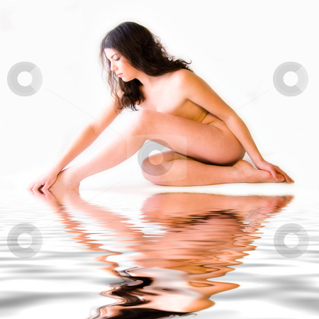 Naked beauty model shaped by water stock photo, Studio portrait of a naked beauty model touching her foot sitting by the pool by Frenk and Danielle Kaufmann
