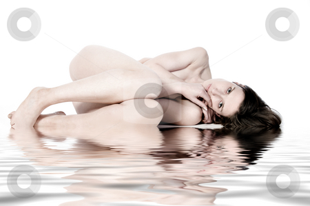 Sleeping naked model by the water stock photo, Studio portrait of a young naked woman resting by the pool by Frenk and Danielle Kaufmann