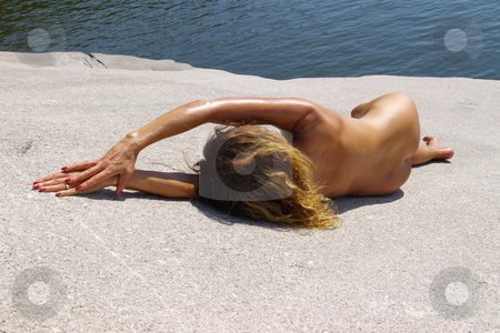 Lady on a Rock stock photo, Nude female model posing on a rock by Rick Olson