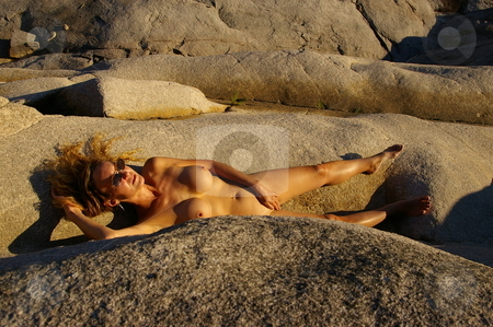 Nude at Sunset stock photo, Nude female model posing on a rocky beach at sunset by Rick Olson