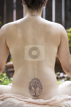 Back of a nude woman meditating stock photo, Back of a nude woman with a Yoga tattoo meditating by Scott Griessel