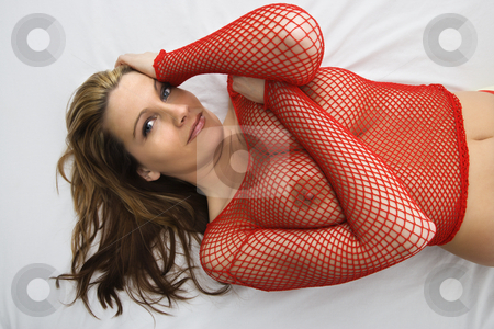 Sexy nude woman. stock photo, Partially nude Caucasian woman lying on bed with mesh shirt. by Iofoto Images