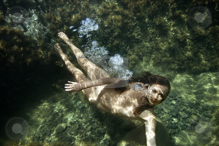 Nude woman underwater. stock photo, Caucasian young nude woman swimming underwater and looking at viewer. by Iofoto Images