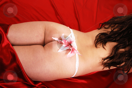 Nude girl on red satin. stock photo, A young woman lying on red satin in white thong and a pink lilly on shooing her nice bottom and long auburn hair. by Horst Petzold