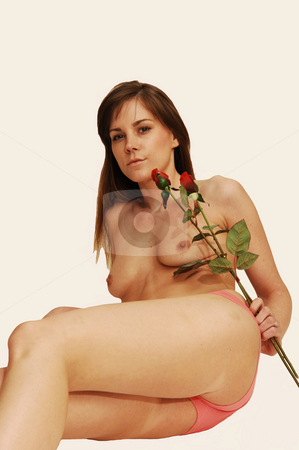 Young lady in pink panties. stock photo, A young pretty lady laying on the floor in pink panties and topless whit her long blond hair and two roses on beige background. by Horst Petzold