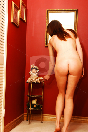 Young nude woman for red wall 20. stock photo, A young pretty nude woman standing with her back and very nice butt in a  hall way with long blond hair for red walls. by Horst Petzold