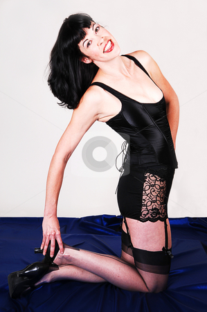 Woman in lingerie. stock photo, An tall young woman in red and black lingerie kneeling on the floor on royal blue silk in the studio for white background. by Horst Petzold