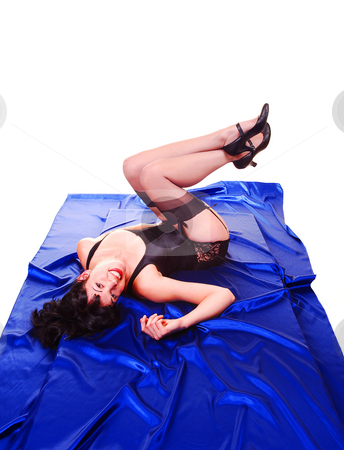 Woman in lingerie. stock photo, An tall young woman in red and black lingerie lying on the floor on royal blue silk in the studio for white background. by Horst Petzold