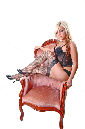 Girl in lingerie. stock photo, Beautiful blond young girl sitting in a pink armchair in black lingerie and fishnet stockings on her nice legs, looking in the camera. by Horst Petzold