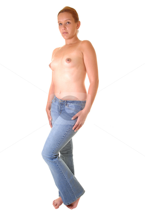 Topless girl. stock photo, A young topless girl with small boobs and an flat stomach and in jeans, standing in front of the camera with her hands on the legs. by Horst Petzold