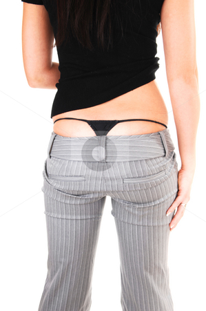 The back and thong of woman. stock photo, The back of an young woman in a gray dress pants and black sweater shooing her black thong underwear, for white background. by Horst Petzold