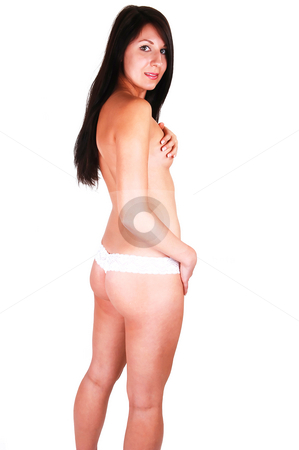 Young girl in lace panties. stock photo, A pretty slim woman, topless and in white lace thongs standing in the studio, looking over her shoulder in the camera. For white background. by Horst Petzold