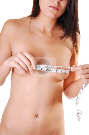 Woman measuring her breasts. stock photo, Pretty slim young woman with long brown hair measuring her breasts and shooing her nice body and stomach. On white background. by Horst Petzold