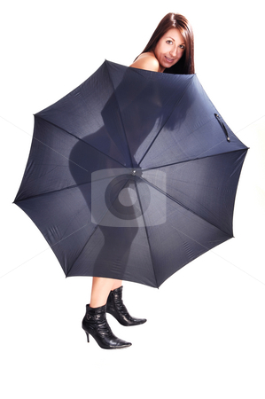 Nude woman with open umbrella. stock photo, Young slim woman standing nude in the studio holding an open umbrella for her, shining trough, body in black boots for white background. by Horst Petzold