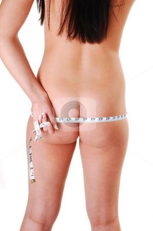 Pretty woman measuring her bottom. stock photo, Young slim naked girl standing in the studio and measuring her butt and the long brown hair running down her back, for white background. by Horst Petzold