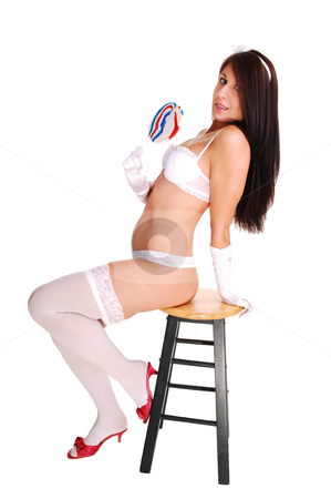 Girl in white lingerie. stock photo, Lovely young woman sitting on a chair in white lingerie and long cloves holding a big jolly pop in her hand, for white background. by Horst Petzold