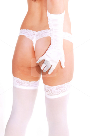 Pretty woman in thongs and stockings. stock photo, Young slim girl standing in the studio in a white panty and stockings and with her white cloves touching the bum, for white background. by Horst Petzold
