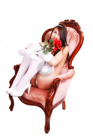 Lingerie girl sitting in armchair. stock photo, Young woman in white lingerie and stockings, with red roses in her hand, sitting in an pink armchair with the legs lifted up. For white background. by Horst Petzold
