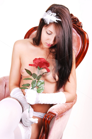 Topless young girl sitting in armchair. stock photo, Beautiful topless young woman with a red rose in her hand, sitting in an pink armchair in white lingerie and stockings. For white background. by Horst Petzold