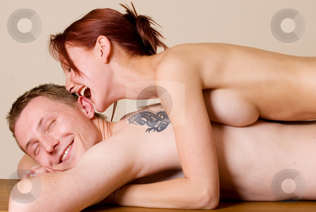 Couple #23 stock photo, Woman on the back of her boyfriend, biting his ear by Sean Nel