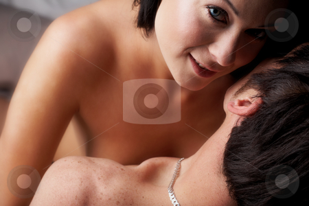 Intimate young lovers stock photo, Young adult Caucasian couple in passionate embrace and undressing each other during sexual foreplay. The woman is wearing blue contact lenses by Sean Nel