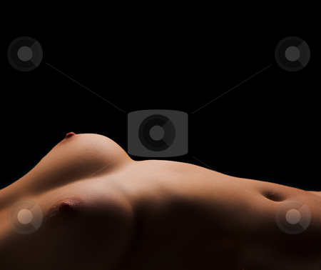 Nude woman lying on her back  stock photo, Torso of a nude woman lying on her back with her breasts and bellybutton visible. High contrast image with black background and a single light source. by Sean Nel